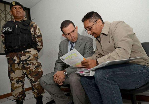 En un receso de la audiencia del juicio de Diego Vallejo, con quien conversa, junto al uniformado.