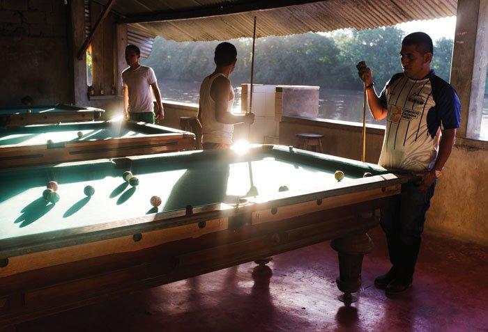 Hombres juegan billar en un establecimiento en Puerto Nuevo, Sucumbíos.
